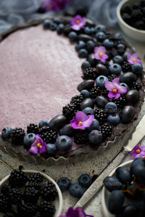 Sweet and tasty tart with fresh blueberries, blackberries and grapes, served on stone background - Stock Photo - Images