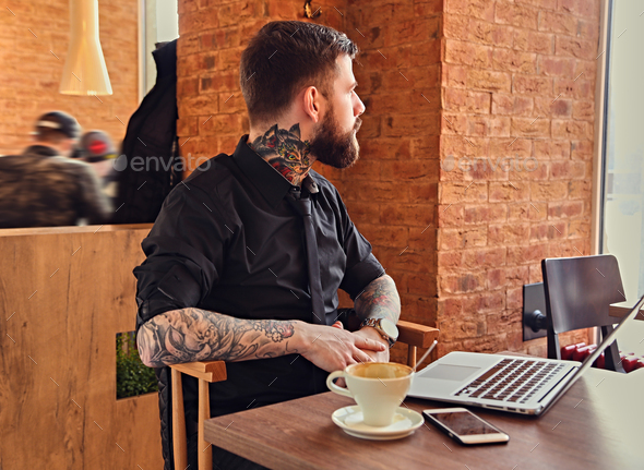 A man relaxing at the table after work with a laptop. - Stock Photo - Images