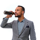 An elegant black American male dressed in a suit drinks beer from a bottle. - PhotoDune Item for Sale