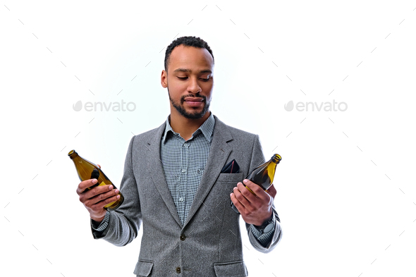 An elegant black American male dressed in a suit holds a craft beer bottle. - Stock Photo - Images