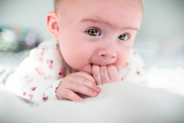 Baby girl on a bed looking at camera - Stock Photo - Images