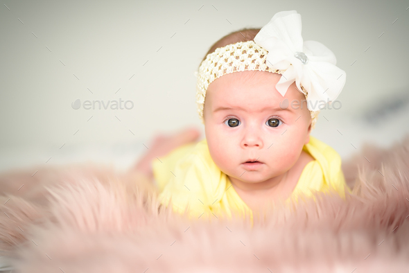 Cute infant girl on bed on belly lifting head looking towards camera - Stock Photo - Images