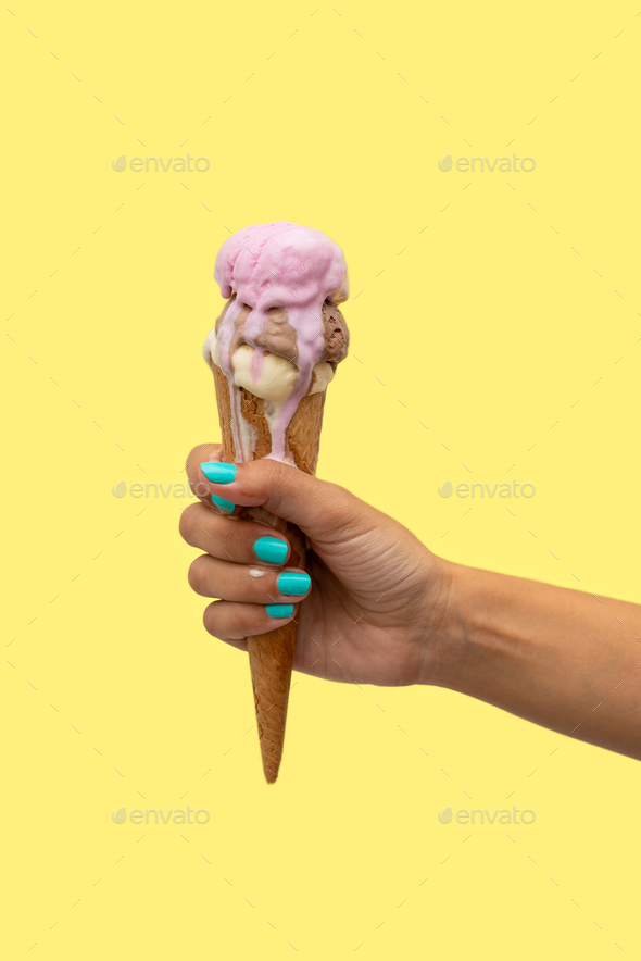 Woman's hand holding an ice cream cone melting in a yellow background - Stock Photo - Images