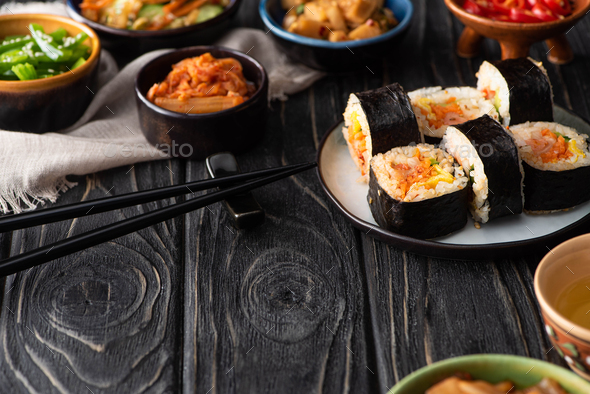 Selective Focus of Delicious Gimbap Near Korean Side Dishes And Cotton Napkin on Wooden Surface - Stock Photo - Images