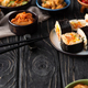 Selective Focus of Delicious Gimbap Near Korean Side Dishes And Cotton Napkin on Wooden Surface - PhotoDune Item for Sale