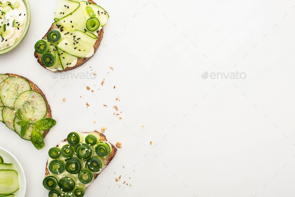 Top View of Fresh Cucumber Toasts With Seeds, Basil Leaves Near Yogurt in Bowl on White Background - Stock Photo - Images