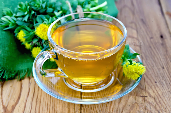 Herbal tea in a cup with a bouquet of Rhodiola rosea on the board - Stock Photo - Images