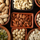 Flat lay view at assorted nuts and seeds in clay bowls on wooden kitchen table - PhotoDune Item for Sale