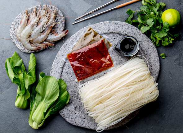 Asian cooking ingredients: rice noodles, pok choy, sauces, raw shrimps. Asian food concept Chinese - Stock Photo - Images