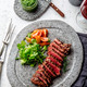 Grilled beef steak medium rare slices on gray stone plate with salad and chimichurri sauce - PhotoDune Item for Sale