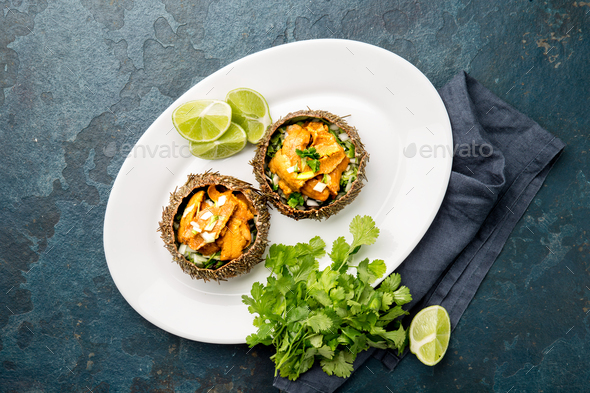 Fresh opened sea urchins. Caviar of sea urchins with onion, cilantro and lemon inside of shell of - Stock Photo - Images