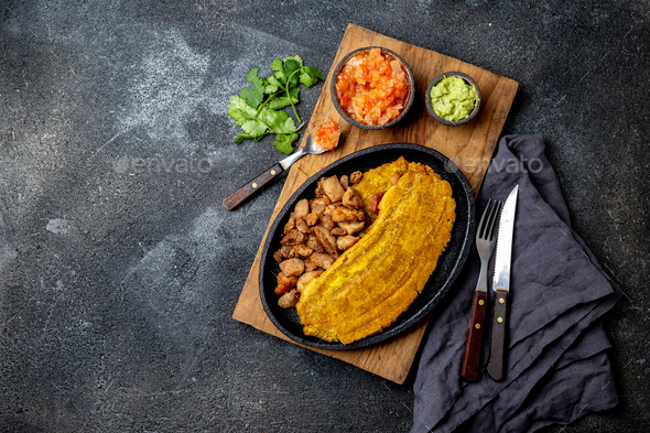 COLOMBIAN CARIBBEAN CENTRAL AMERICAN FOOD. Patacon or toston, fried and flattened whole green - Stock Photo - Images