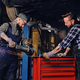 Two b mechanics working with an angle grinder in a garage. - PhotoDune Item for Sale