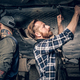 Two mechanics working under the car in a garage. - PhotoDune Item for Sale