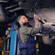 Bearded  mechanic working with the car's chassis in a workshop. - PhotoDune Item for Sale