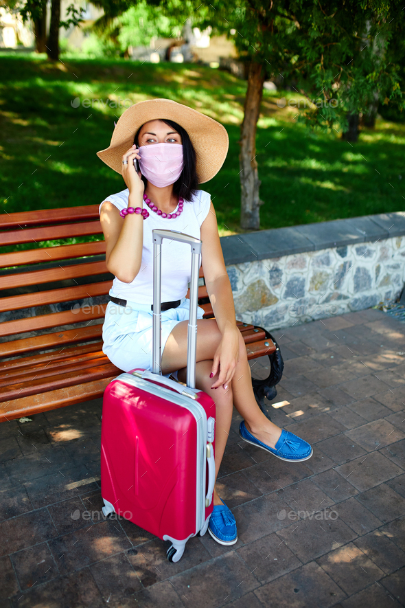Woman protective mask, in the park outdoor with a suitcase, talking on a mobile - Stock Photo - Images