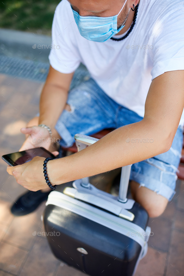 Man in protective mask, sitting in the park outdoor with a suitcase, and a mobile phone - Stock Photo - Images