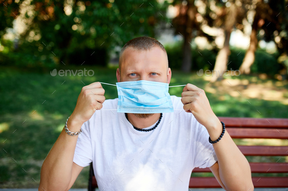 Portrait of man takes off protective mask in the park outdoor in the city - Stock Photo - Images