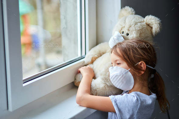 Little girl holding and hugging teddy bear in mask near the window. - Stock Photo - Images