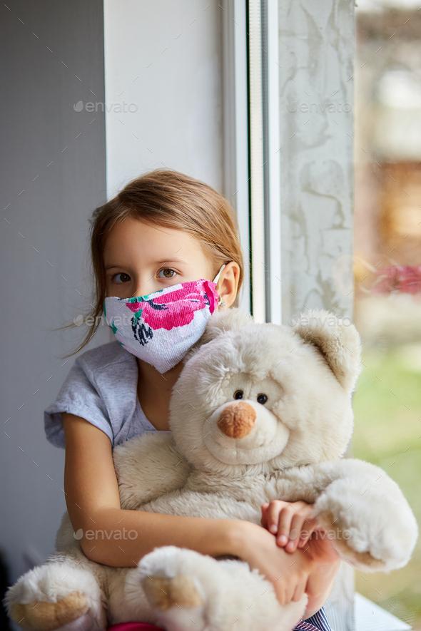 Little girl, child in mask with teddy bear sits on windows, coronavirus quarantine - Stock Photo - Images