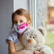Little girl, child in mask with teddy bear sits on windows, coronavirus quarantine - PhotoDune Item for Sale