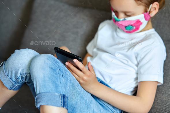 Little girl in protection mask using, play tablet or learning with video call online - Stock Photo - Images
