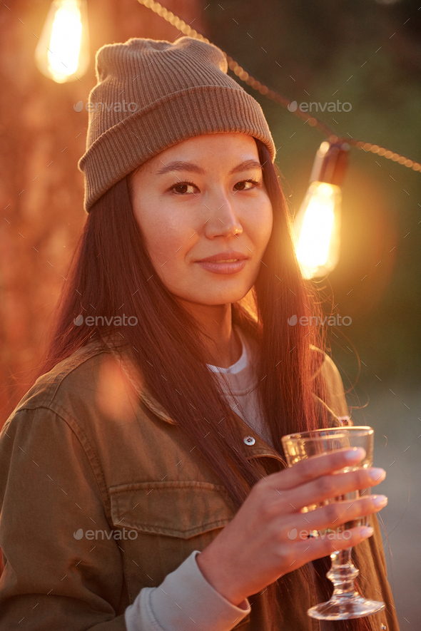 Happy Asian girl with dark long hair toasting with drink against lights - Stock Photo - Images