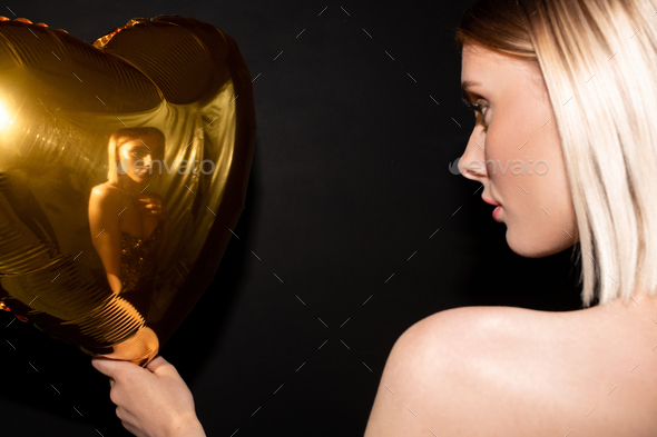 Blond girl looking at her reflection in heart shaped balloon of golden color - Stock Photo - Images