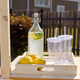 Bottle of homemade lemonade, pile of fresh lemons and two empty plastic glasses - PhotoDune Item for Sale