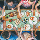 eating and leisure concept - group of people having dinner at table with food - PhotoDune Item for Sale