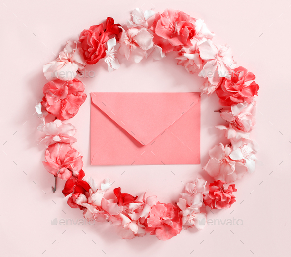 Red envelope in a frame of pink flowers over a pink background - Stock Photo - Images