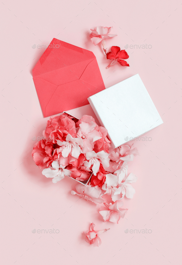 Red envelope and gift box full of flowers  over a pink background - Stock Photo - Images