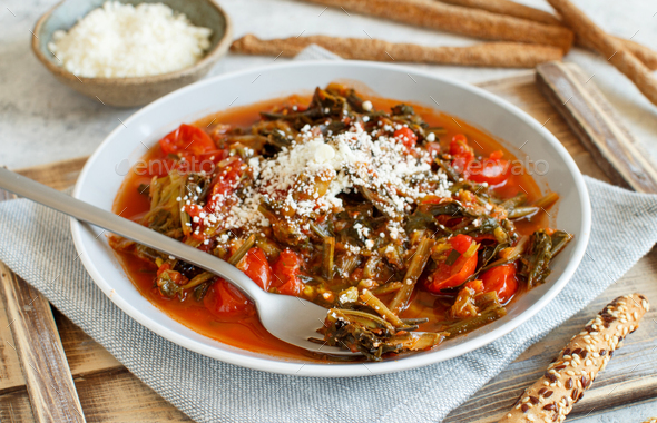 Sauteed green cicory and tomatoes topped with caccioricotta cheese - Stock Photo - Images