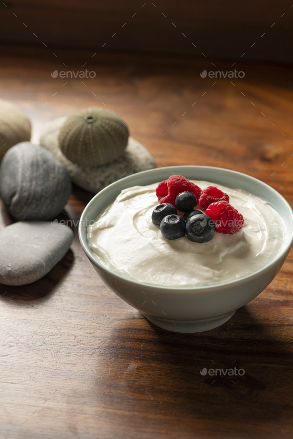 Yogurt with Fresh Raspberries and Blueberries in a Bowl on a Wooden Table - Stock Photo - Images