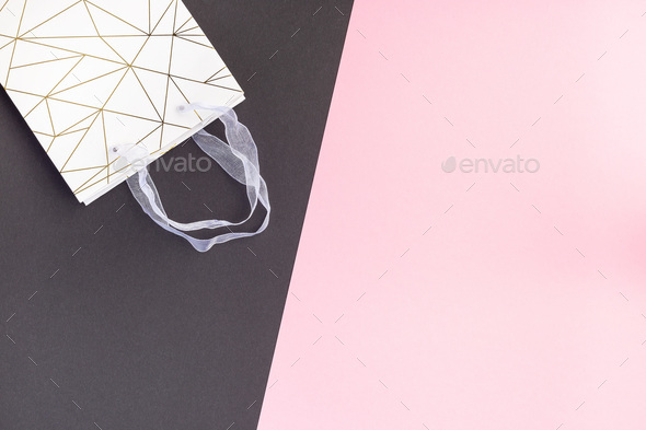 Paper shopping bag on pink and black paper, horizontal, copy space - Stock Photo - Images