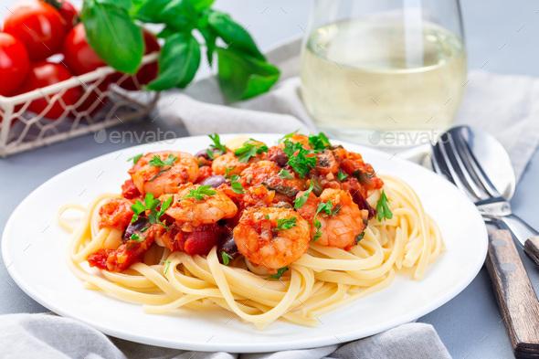 Italian linguine Puttanesca, pasta with shrimps in tomato basil sauce horizontal - Stock Photo - Images