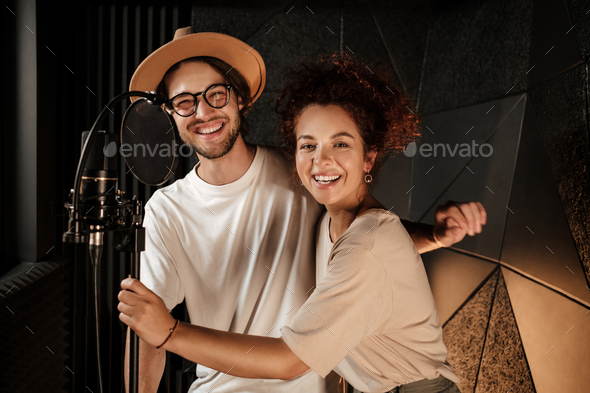 Attractive stylish musicians happily looking in camera working together on new music album in studio - Stock Photo - Images