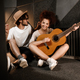 Young attractive man and woman happily playing new song on guitar sitting on floor in studio - PhotoDune Item for Sale