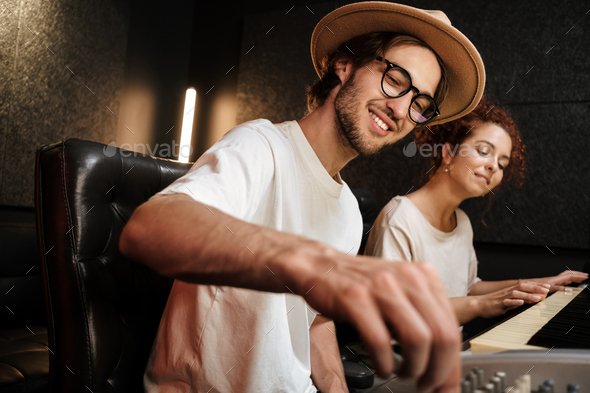 Young stylish people creating music in modern sound recording studio - Stock Photo - Images
