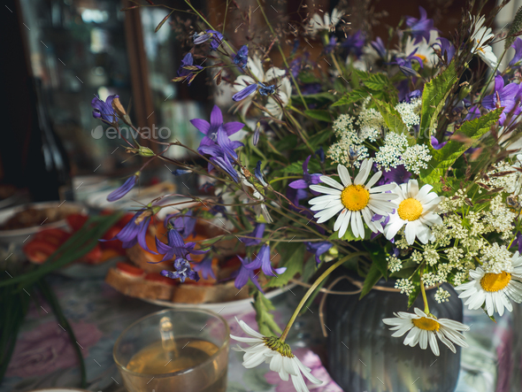 Table setting with wild flowers bouqet.Cottagecore - Stock Photo - Images