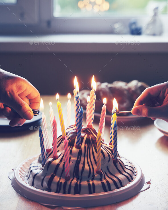 Colorful birthday cake with with hands burning nineteen candles home party - Stock Photo - Images