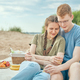 Young couple enjoying picnic on beach embracing and holding cups - PhotoDune Item for Sale