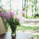 Bouquet of forest flowers in vase on table near camper in forest - PhotoDune Item for Sale