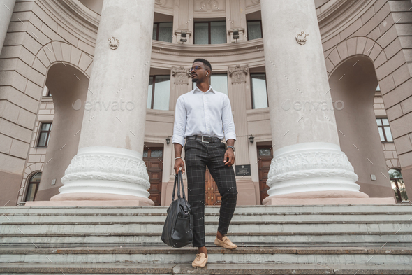 Handsome elegance stylishly dressed young black man with wireless earphones and leather bag in hand. - Stock Photo - Images