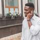 Young stylishly dressed black male, enjoying music with wireless earphones walking outdoors - PhotoDune Item for Sale