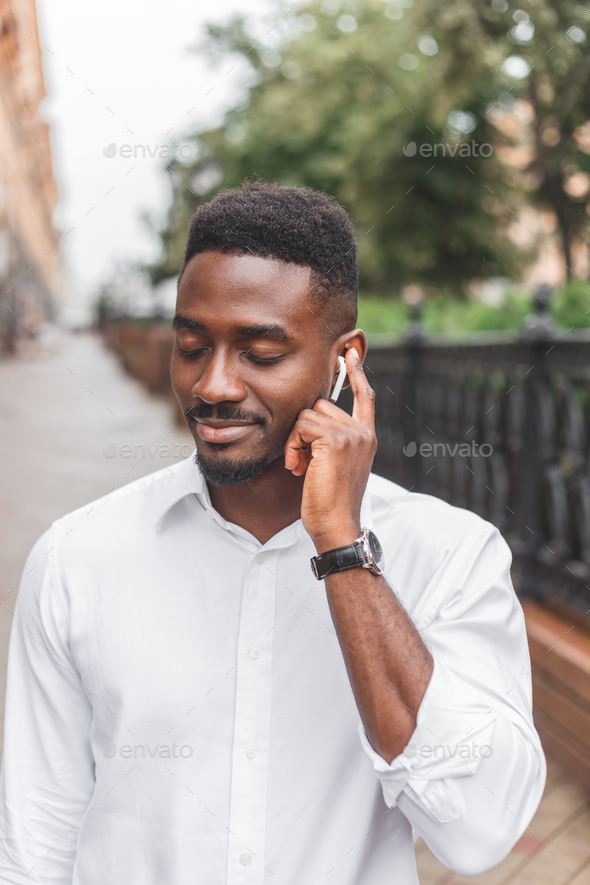 Young stylishly dressed black male, enjoying music with wireless earphones walking outdoors - Stock Photo - Images