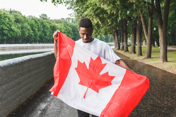 Handsome Afro American man with Canadian flag, standing outdoors. - Stock Photo - Images