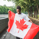 Handsome Afro American man with Canadian flag, standing outdoors. - PhotoDune Item for Sale