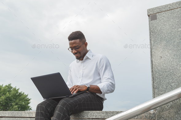 Handsome young businessman working with laptop outdoors at business building - Stock Photo - Images