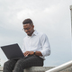 Handsome young businessman working with laptop outdoors at business building - PhotoDune Item for Sale